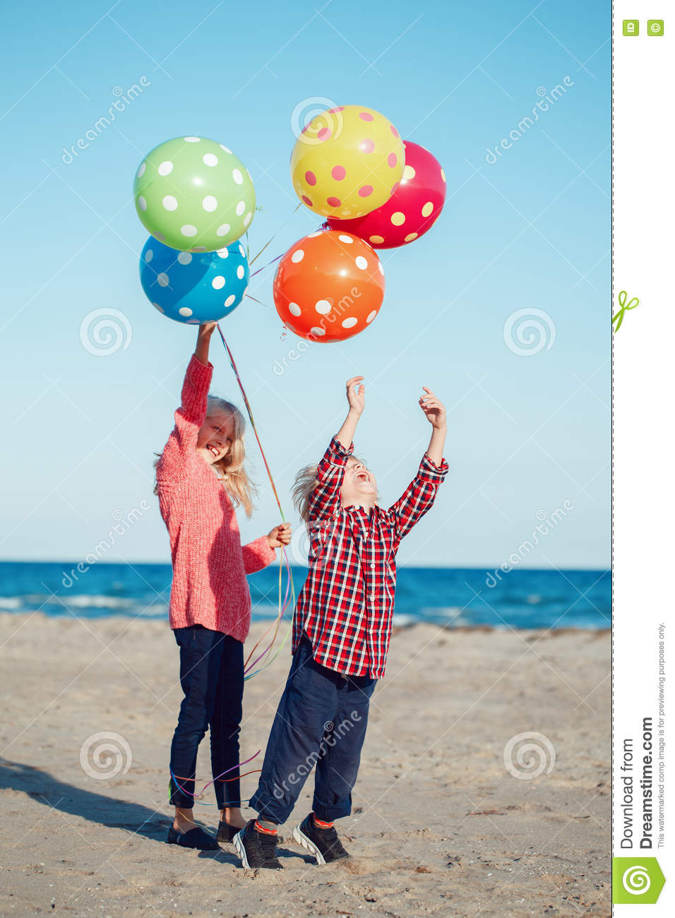 Group portrait of two funny white Caucasian children kids with colorful bunch of balloons, playing running on beach on sunset