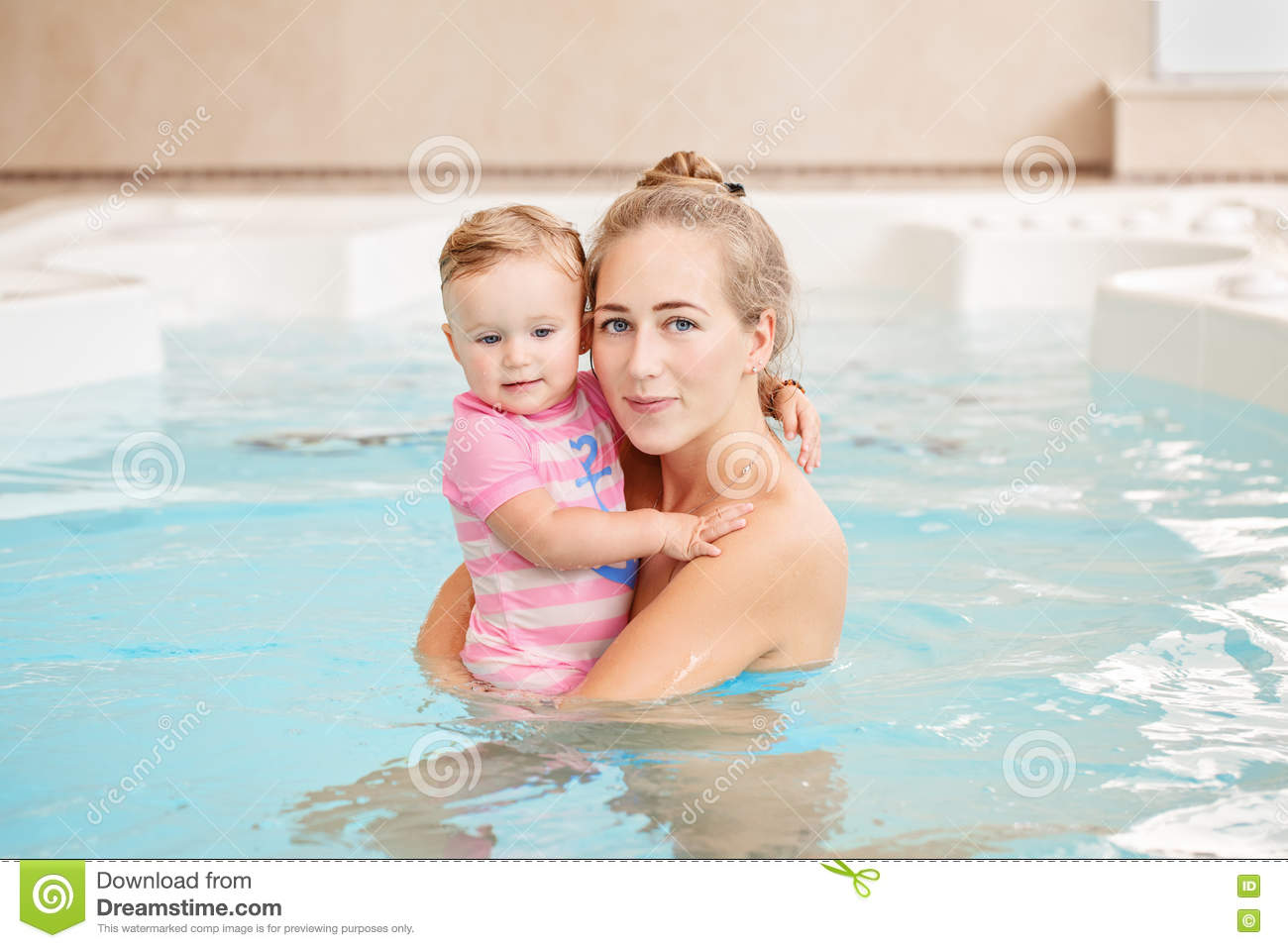 Group portrait of white Caucasian mother and baby daughter playing in water in swimming pool