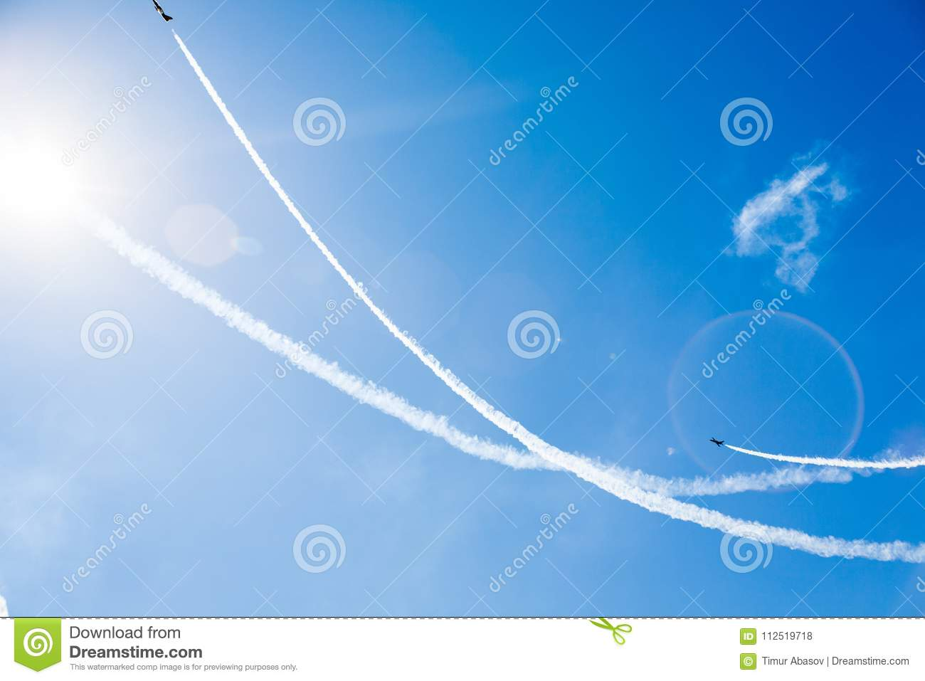 A group of professional pilots of military aircraft of fighters on a sunny clear day shows tricks in the blue sky, leaving beauti