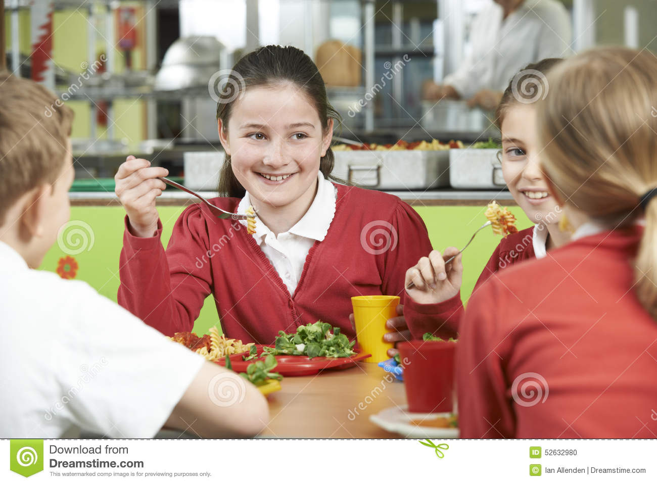 Group of pupils sitting at table in school cafeteria for Group lunch
