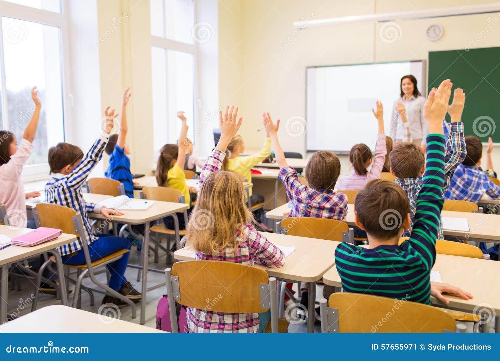 d7f15d2d31d Group of school kids raising hands in classroom stock image