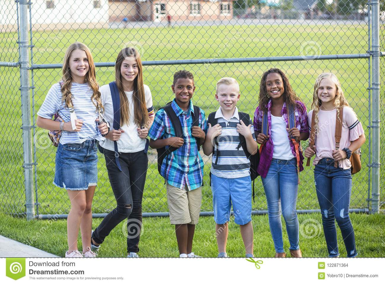Group of school kids smiling while standing in a elementary school playground
