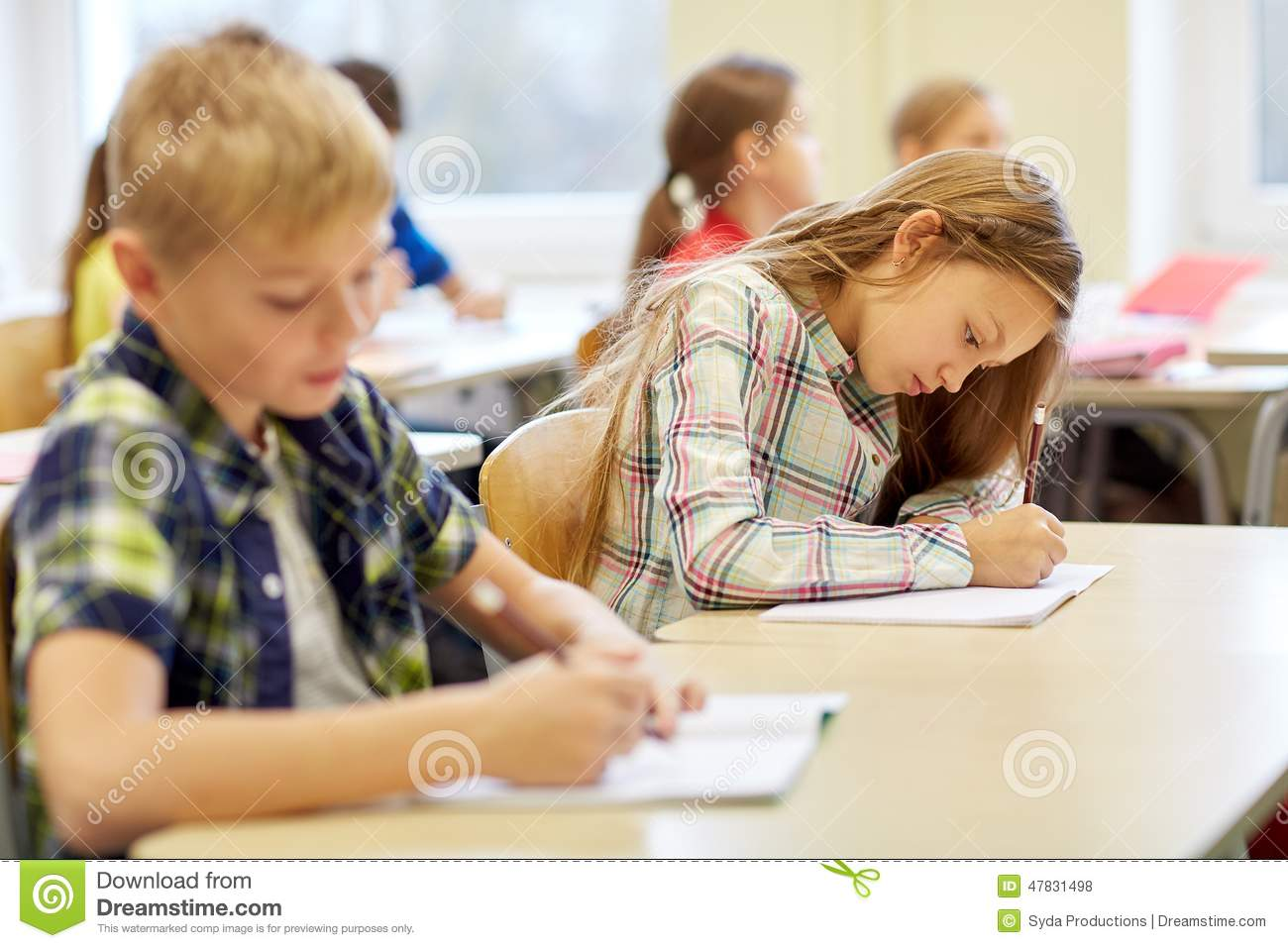Elementary Classrooms Writing : Group of school kids writing test in classroom stock photo