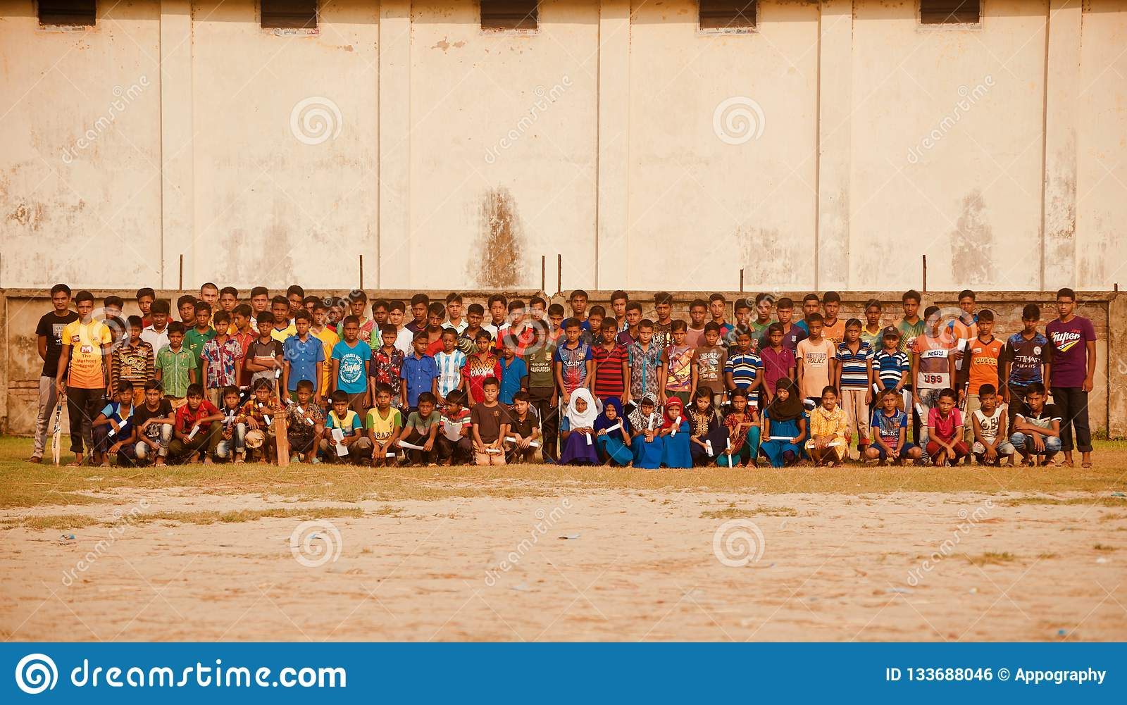 A group of school students sitting in a ground