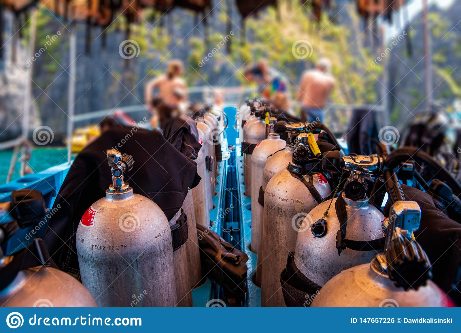 Scuba divers getting ready for diving on a boat full of equipment, Thailand