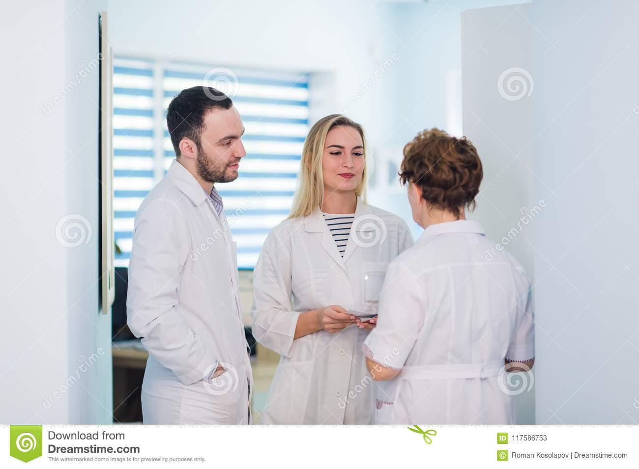 Group of senior doctors and young nurses examining medical report of patient. Team of doctors working together on