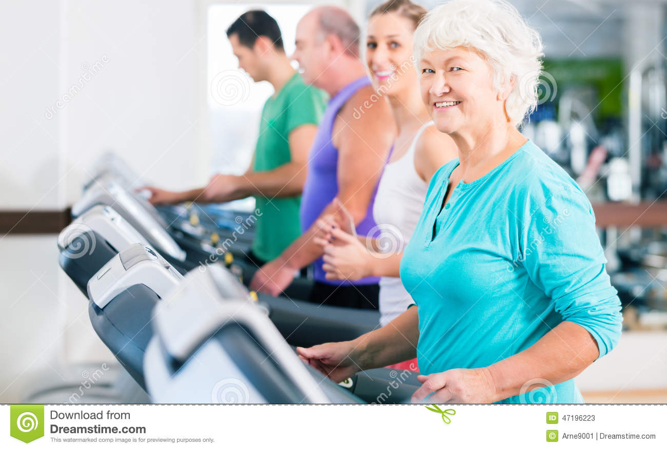 ... and young men and women people on treadmill in fitness gym running for