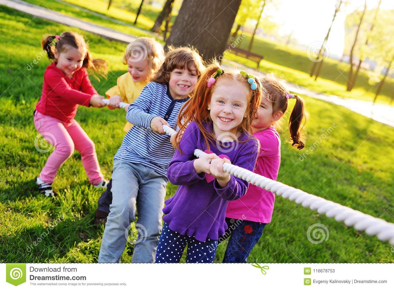 A Group Of Small Preschool Children Play Tug War In The Park