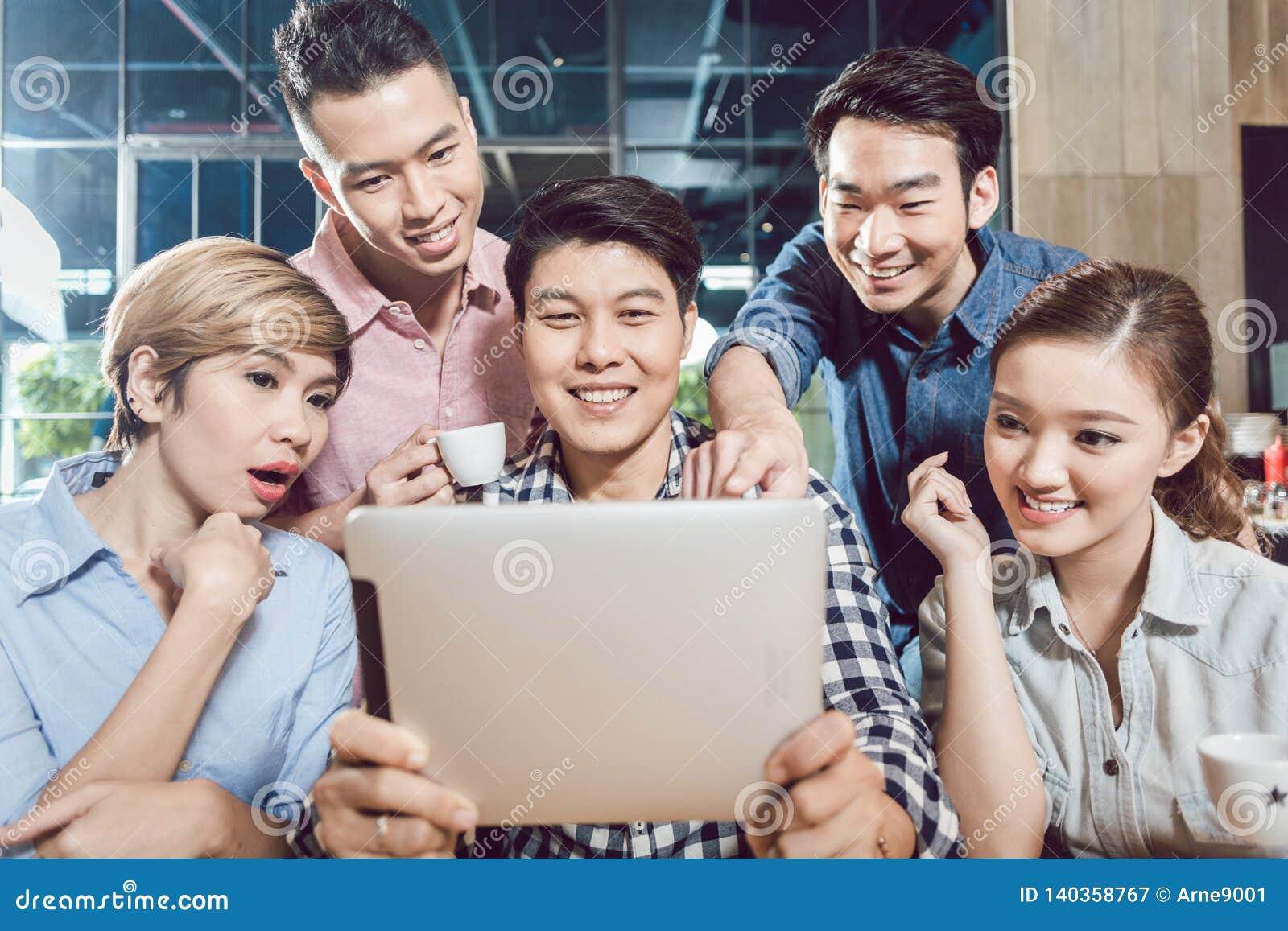 Group of friends enjoying on digital tablet