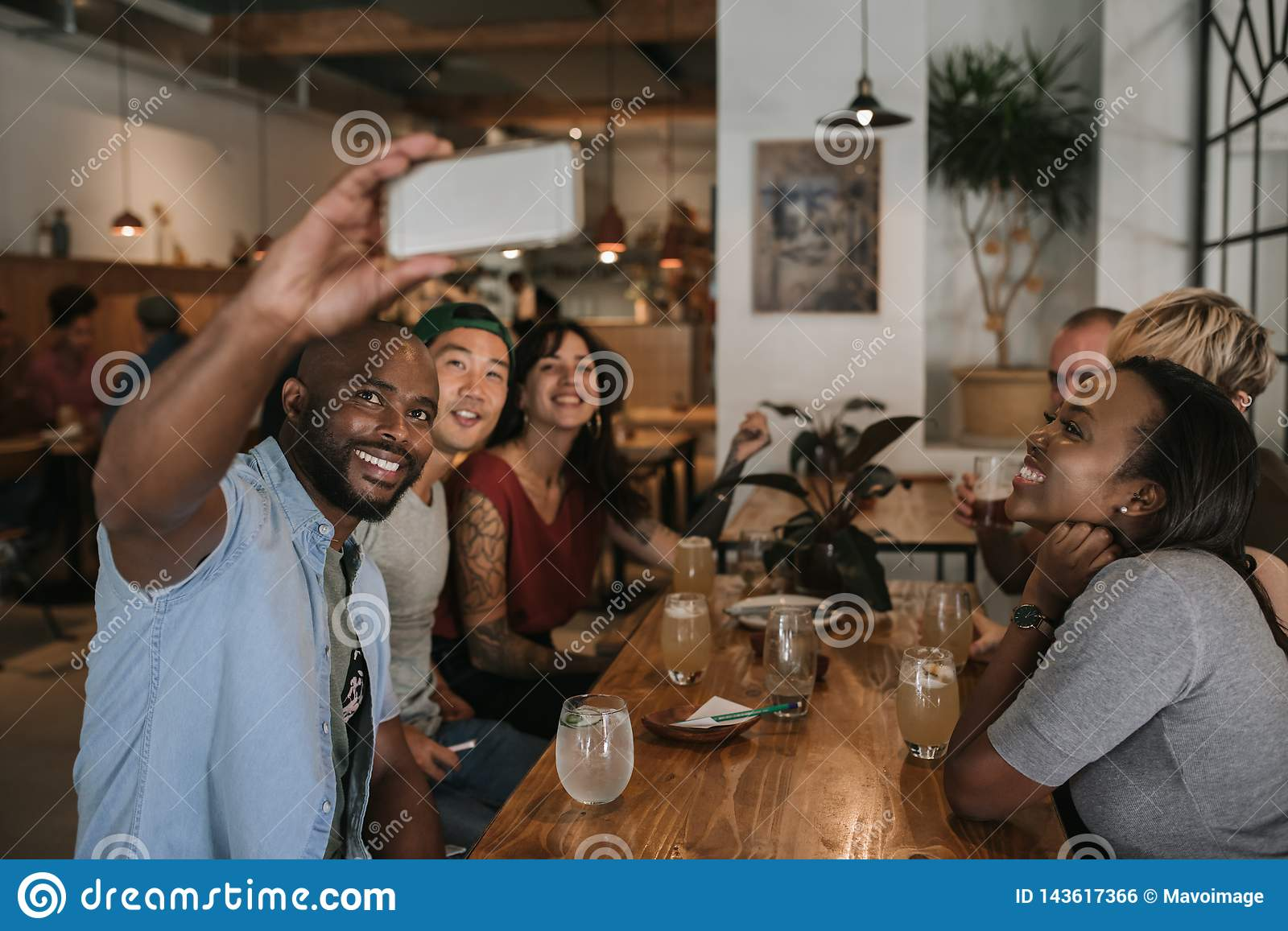Group of smiling friends taking selfies together in a bar