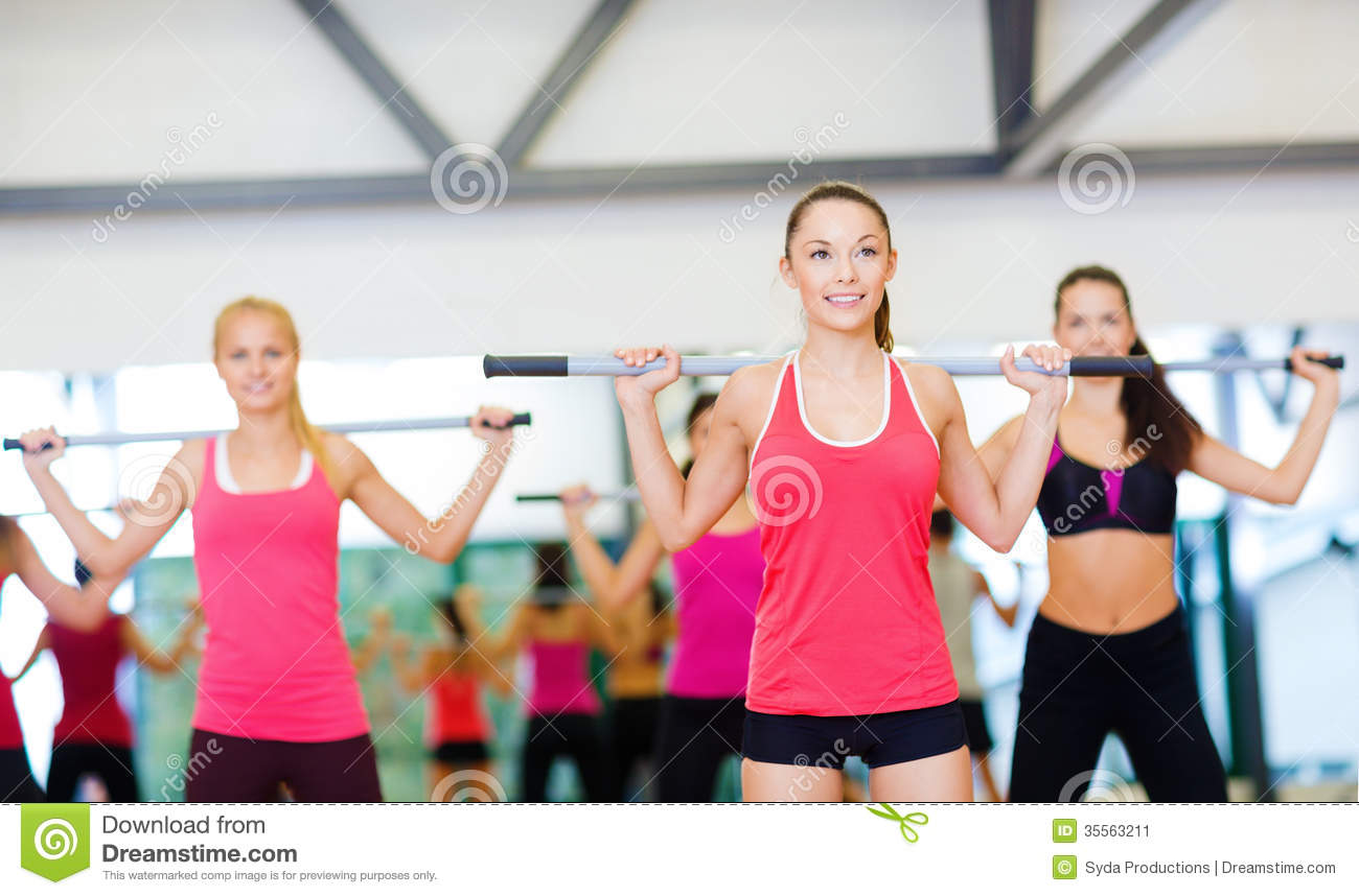 Group of smiling people working out with barbells stock for Gym life fitness