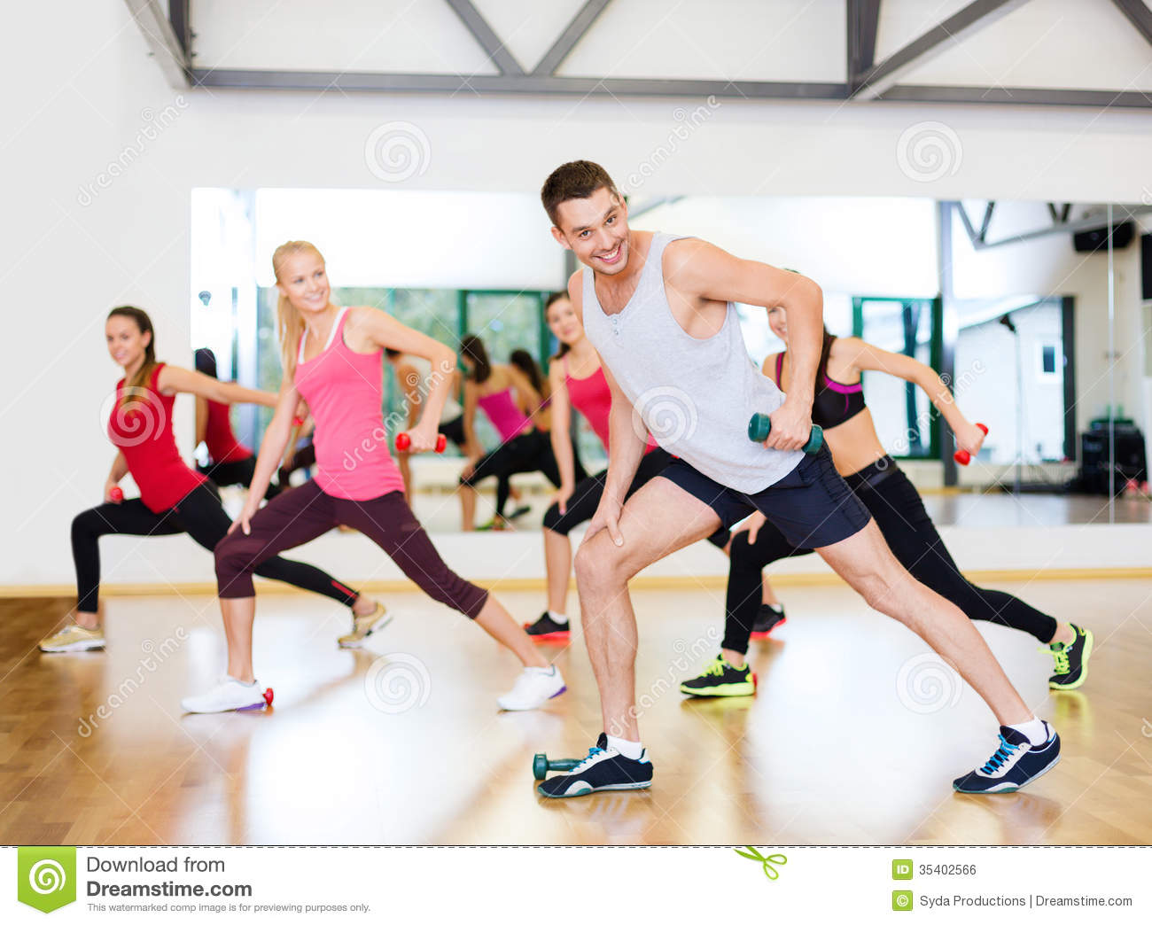 Group of smiling people working out with dumbbells royalty for Gym life fitness
