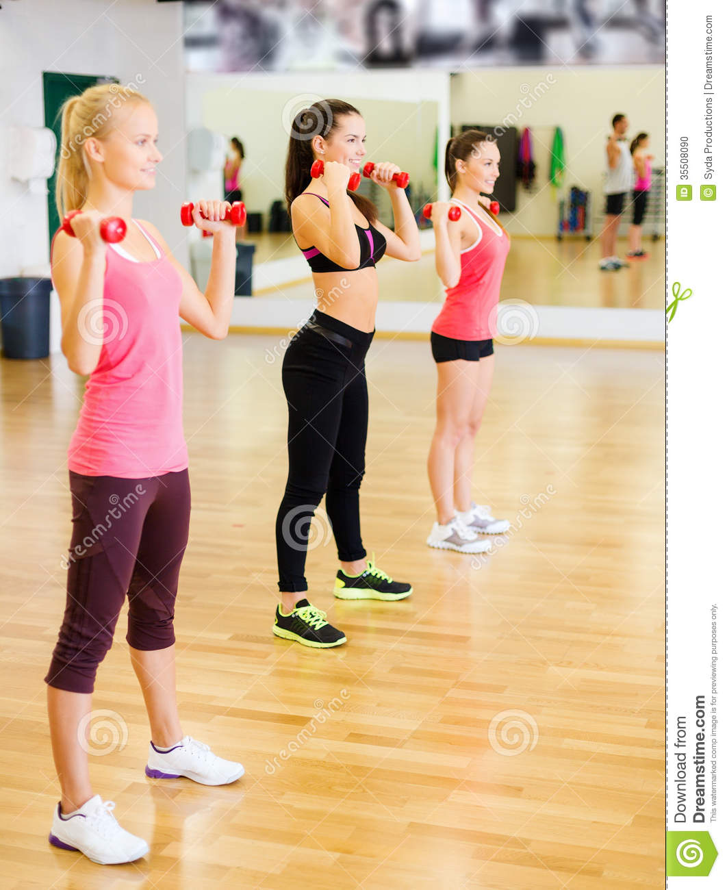 Working Out: Group Of Smiling People Working Out With Dumbbells Stock