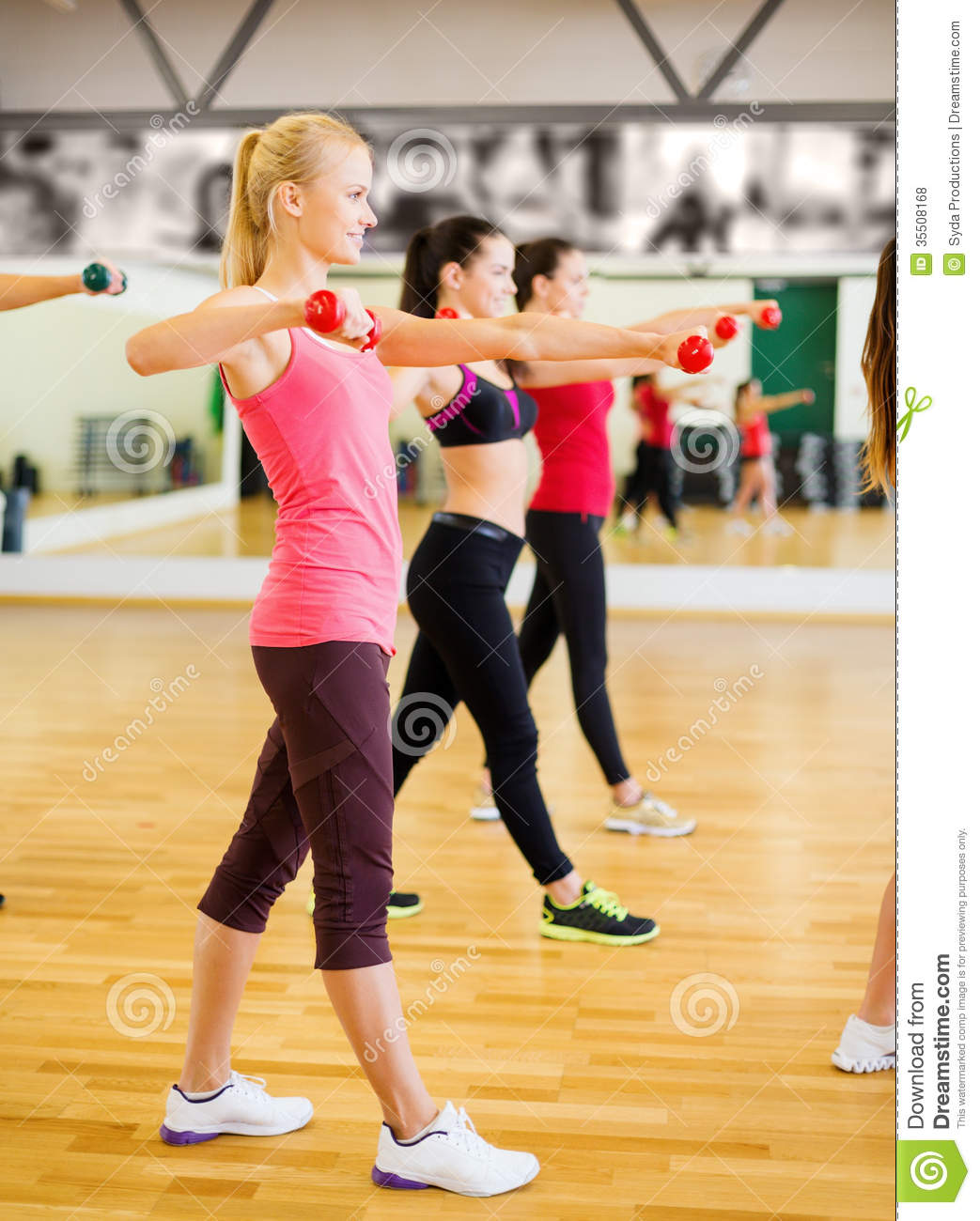 Group of smiling people working out with dumbbells stock for Gimnasio sport gym