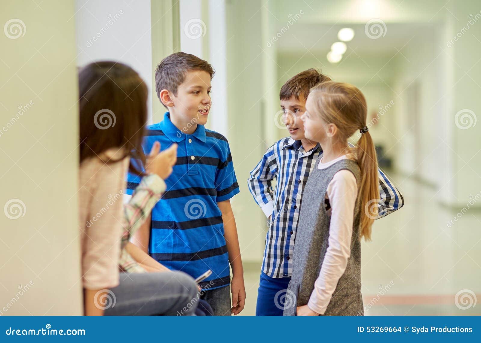 Group Of Smiling School Kids Talking In Corridor Stock ...