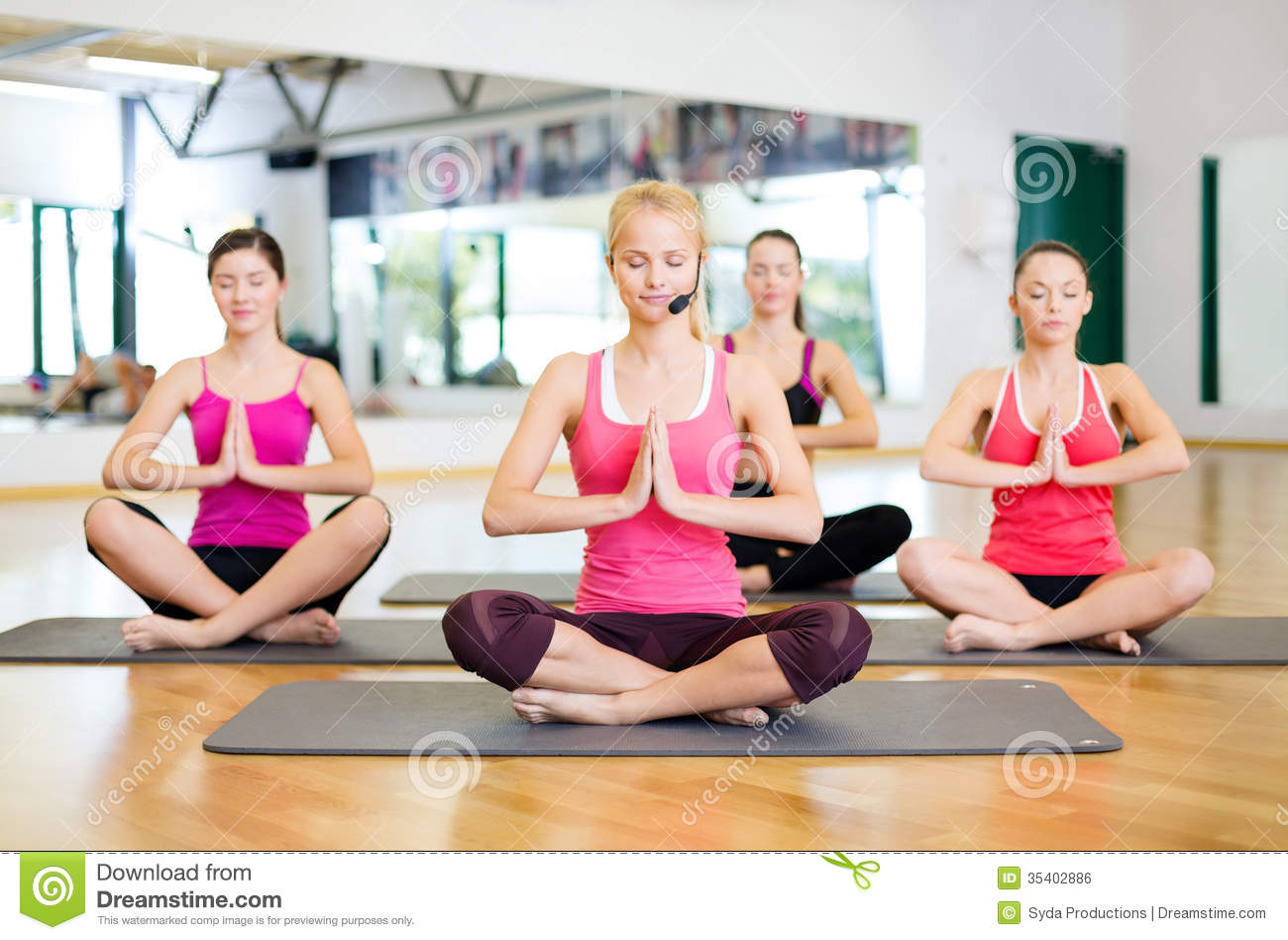 Group Of Smiling Women Meditating In Yoga Pose Stock Photo ...