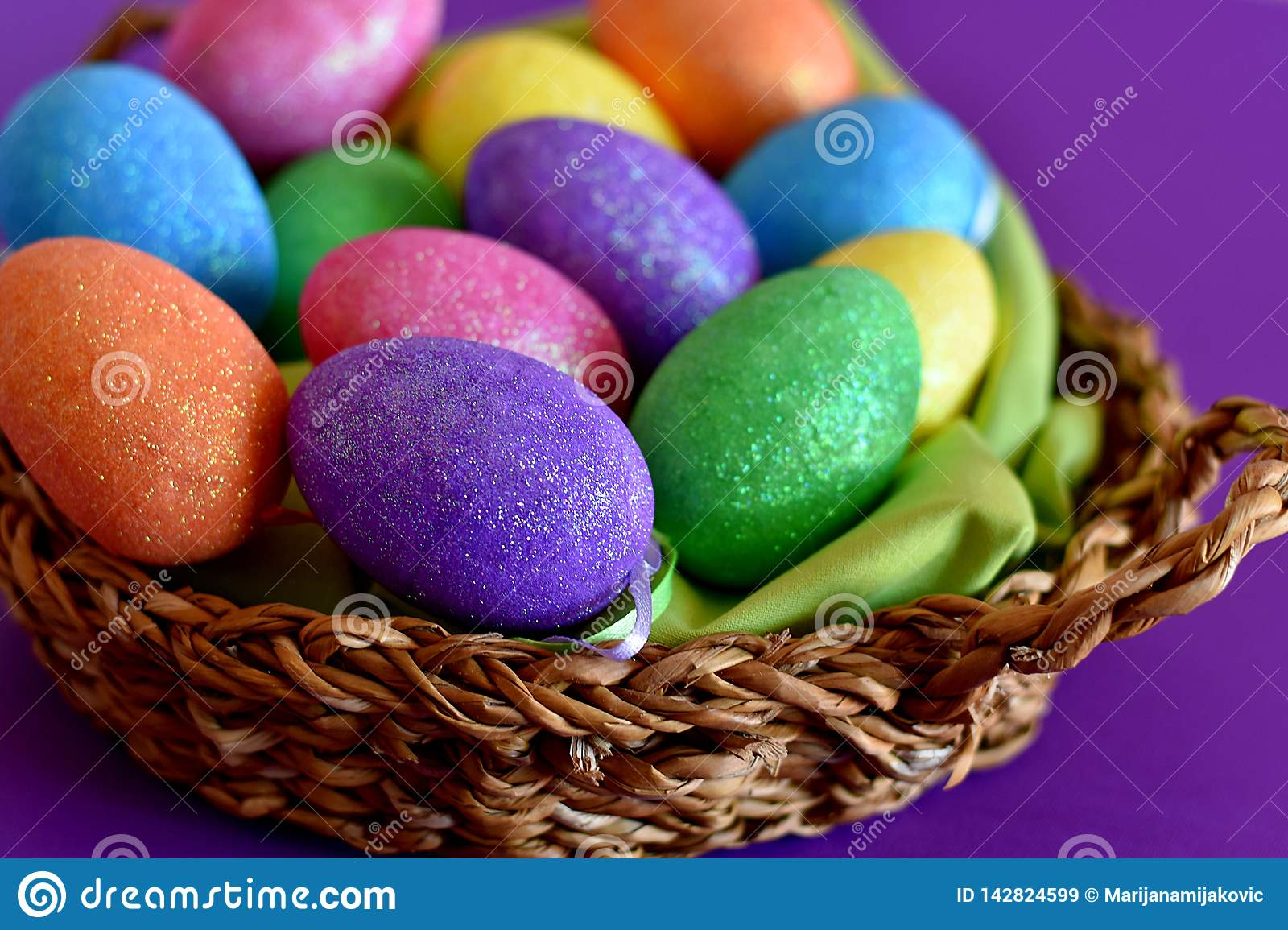 Sparkling glittering colored candy Easter eggs in a wicker basket