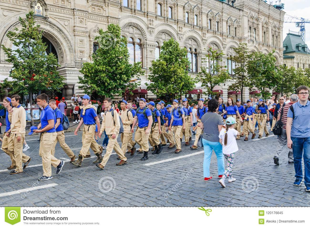 A group of teenagers-tourists in the uniform of the summer camp are going in pairs on the Red square
