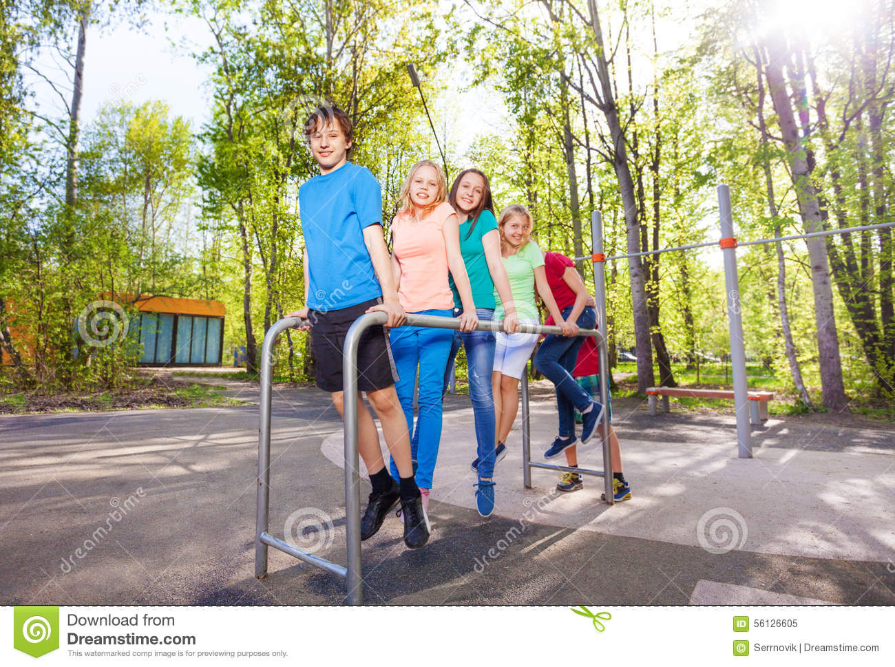 Hanging teens on horizontal bar at sports ground stock for Hanging groups of pictures