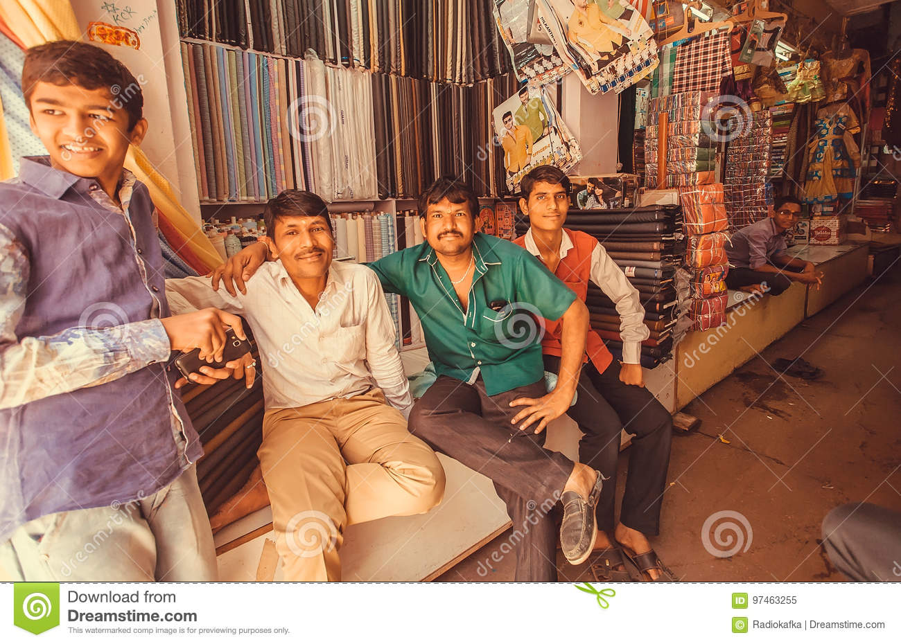 Group of textile market traders relaxing near traditional male and female clothing stores