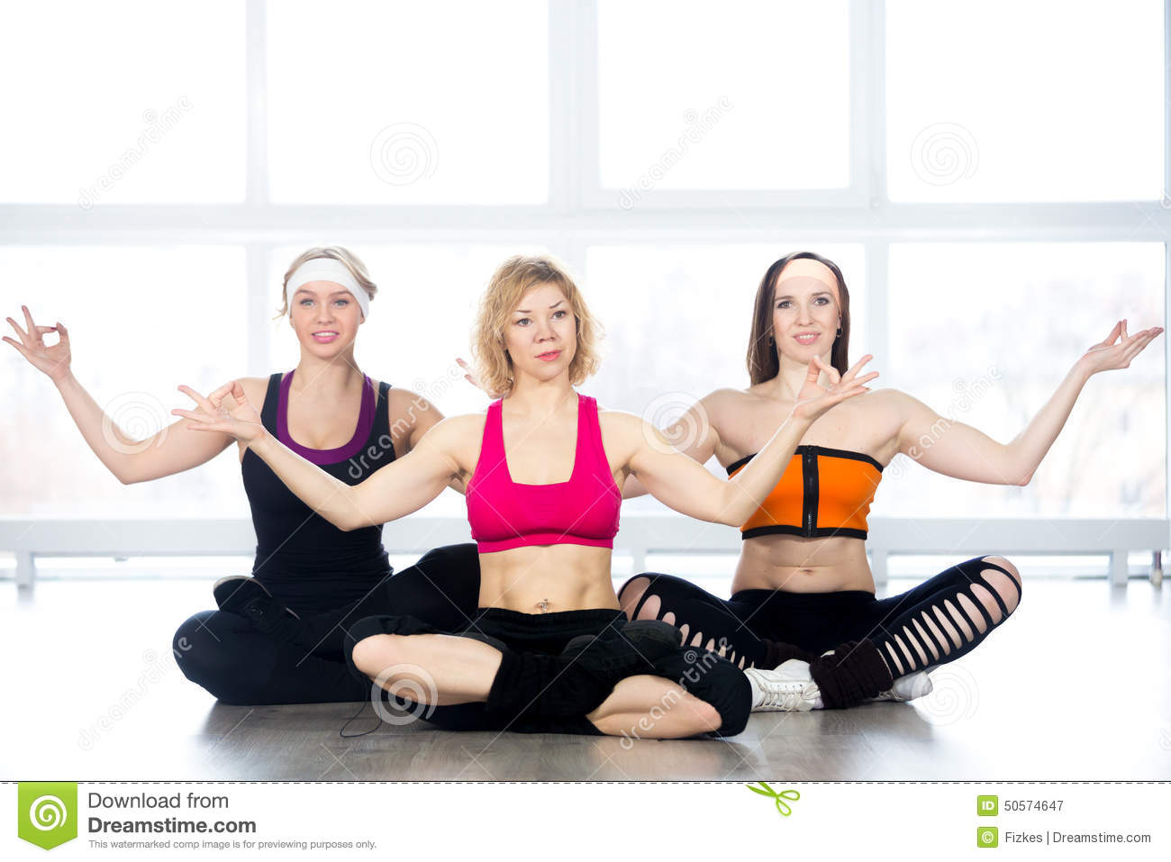 Group Of Three Females Practice Yoga In Class Stock Image