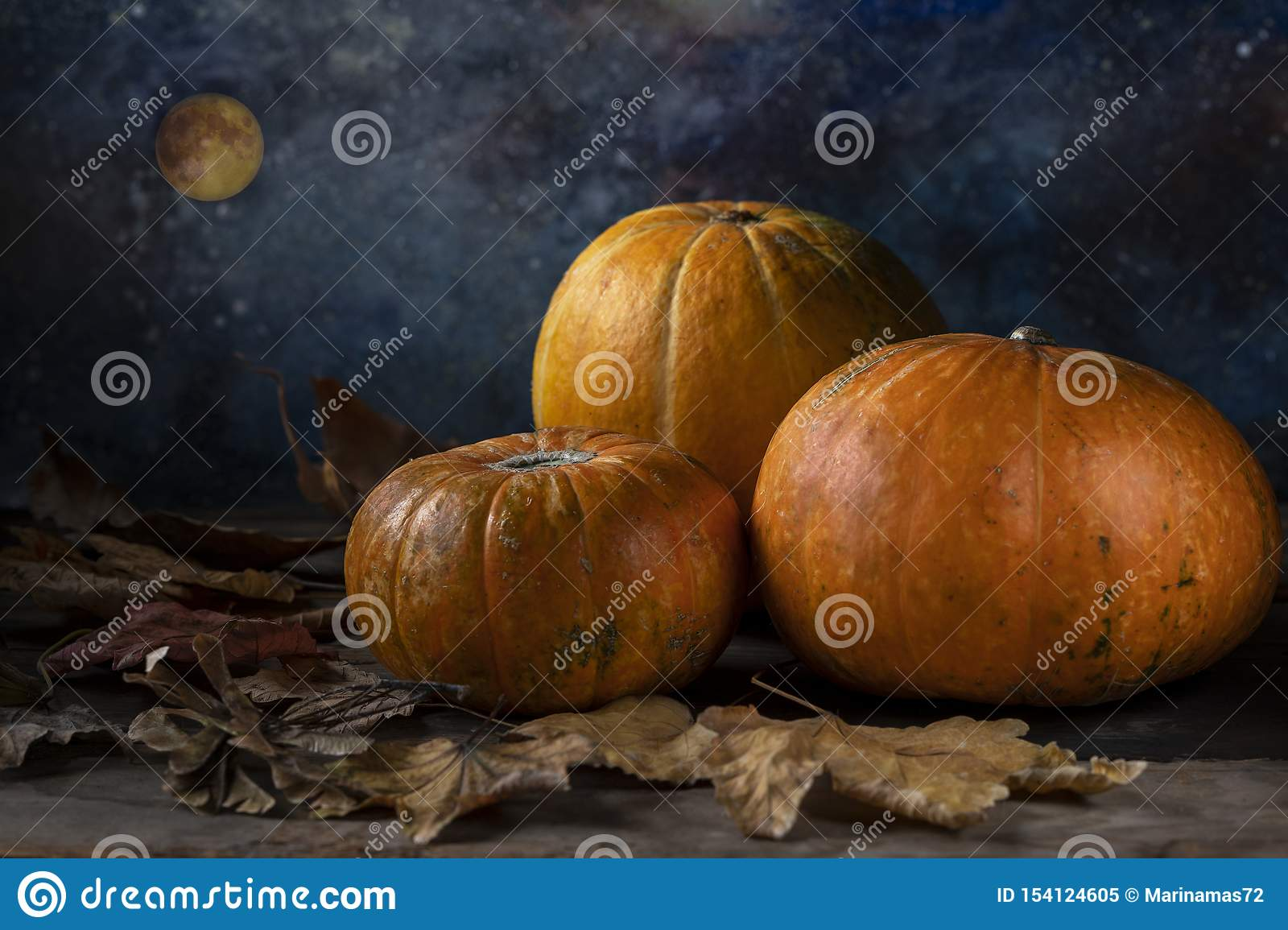 A group of three pumpkins and fallen dry leaves
