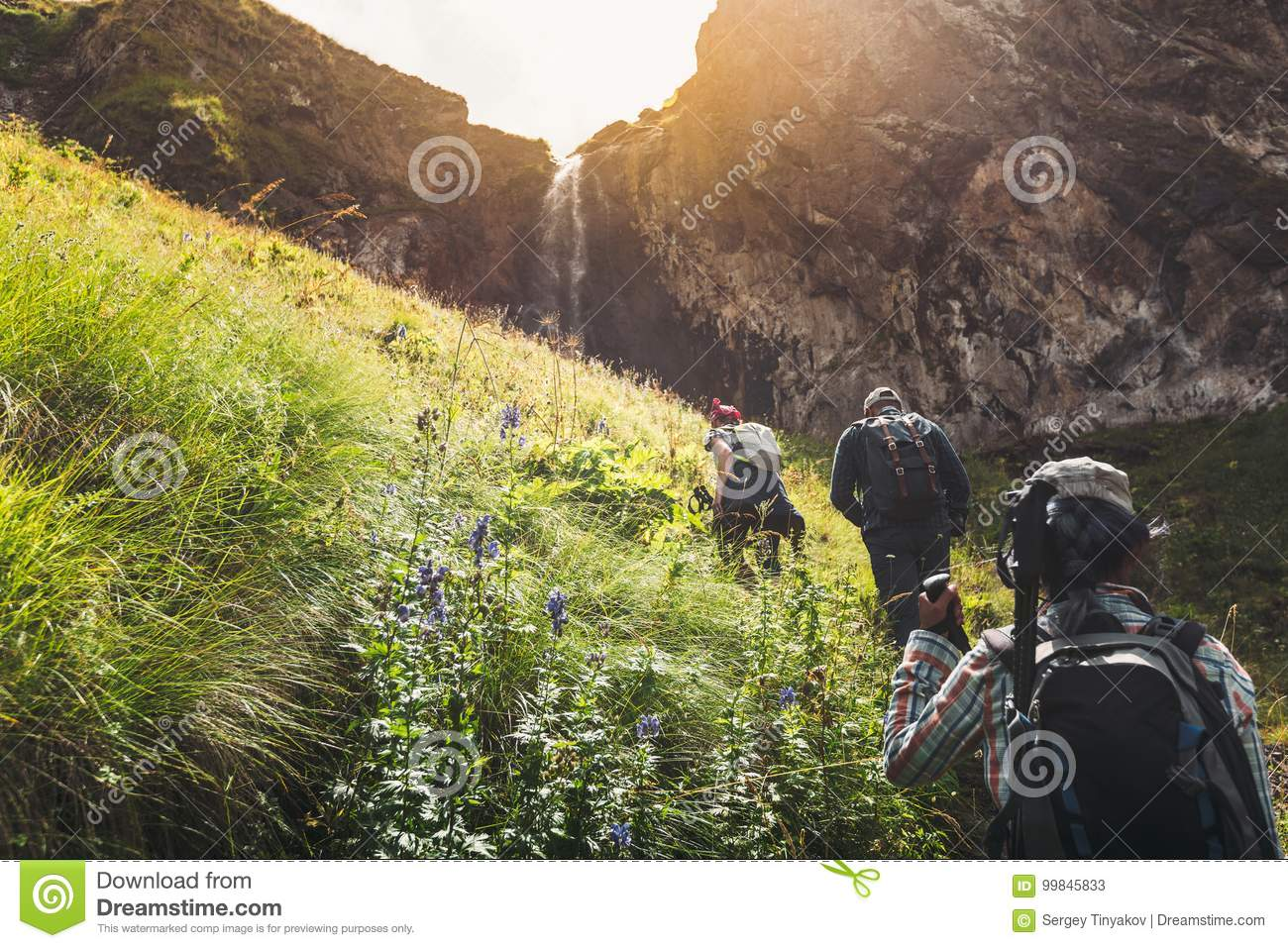 Group Of Tourists Walking Uphill To Waterfall. Travel Adventure Outdoor Concept