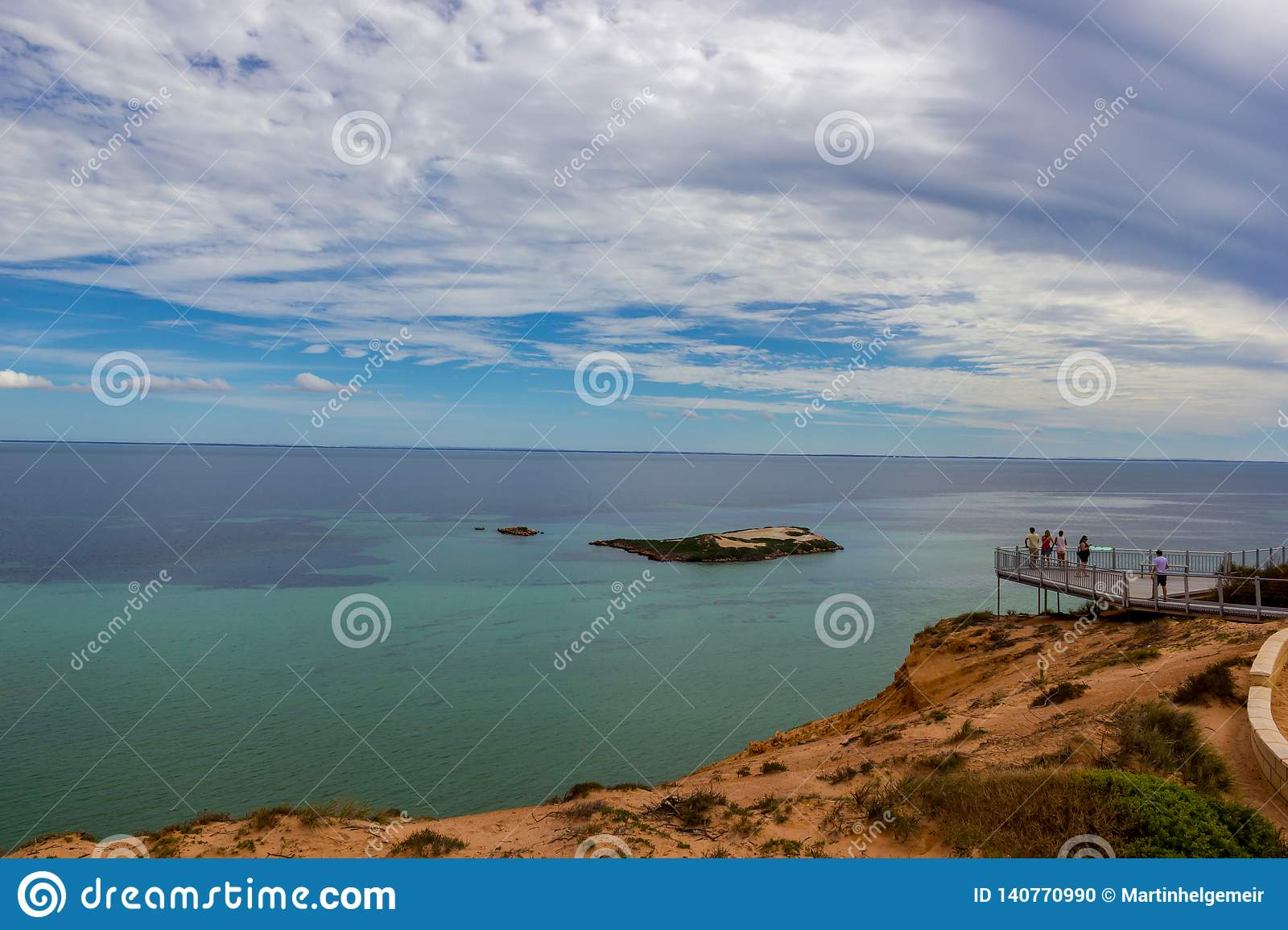 A Group of tourists at a Lookout platform in Monkey Mia, Western Australia. Caucasian girl enjoying cliffs of Indian