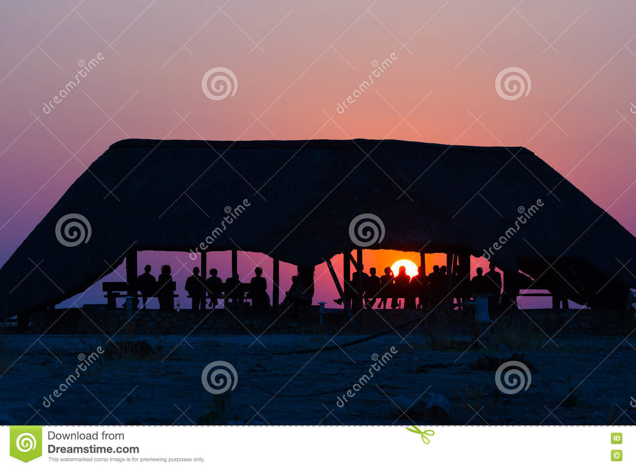 Group of tourists watching colorful sunset under shelter. Tourist resort in Africa. Backlight, silhouette, rear view