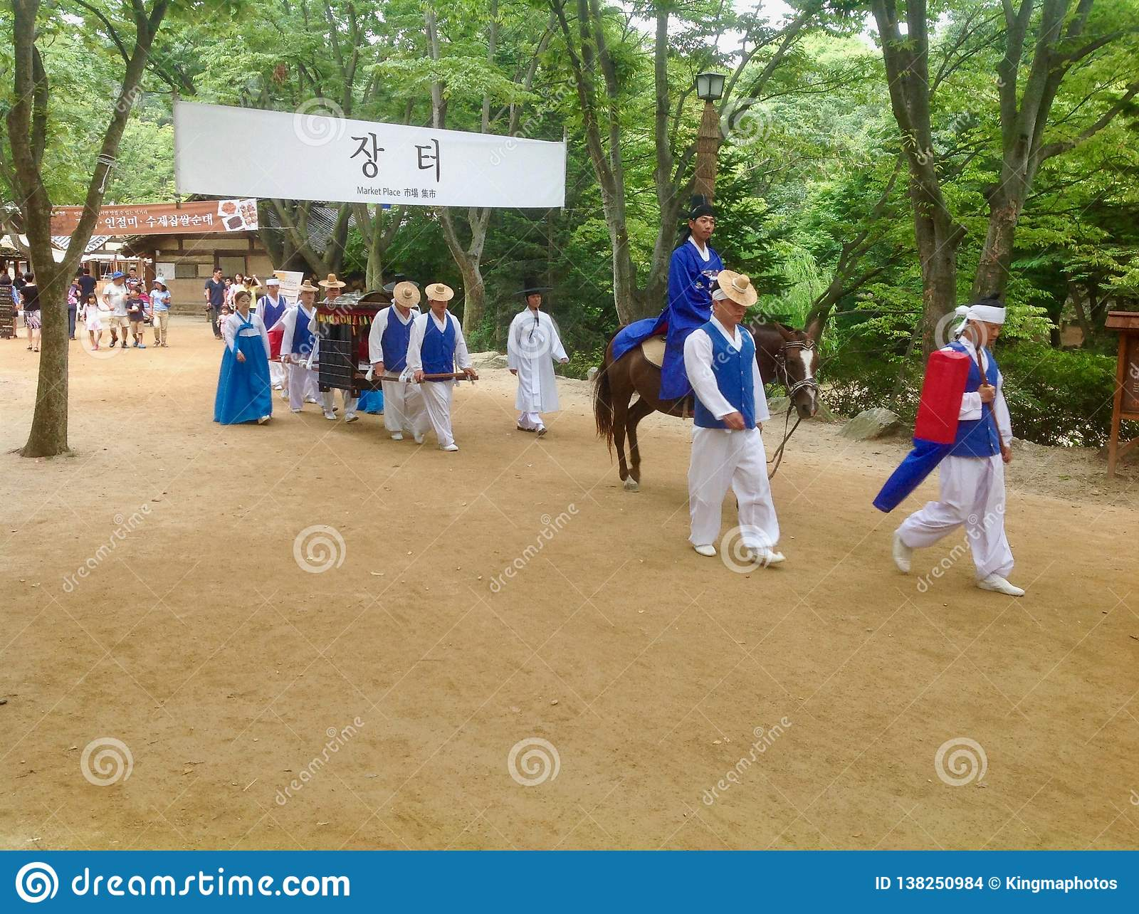A group of traditionally dressed Koreans walk through the village for the tourist show