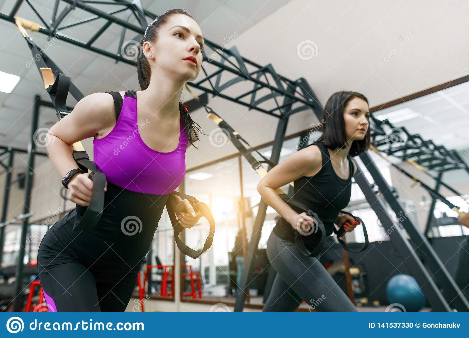 Group Training With Loops In The Gym, Two Young Attractive Fitness Women  Doing Cross Fit With Straps System. Sport, Teamwork, Stock Photo - Image of  lifestyle, healthy: 141537330