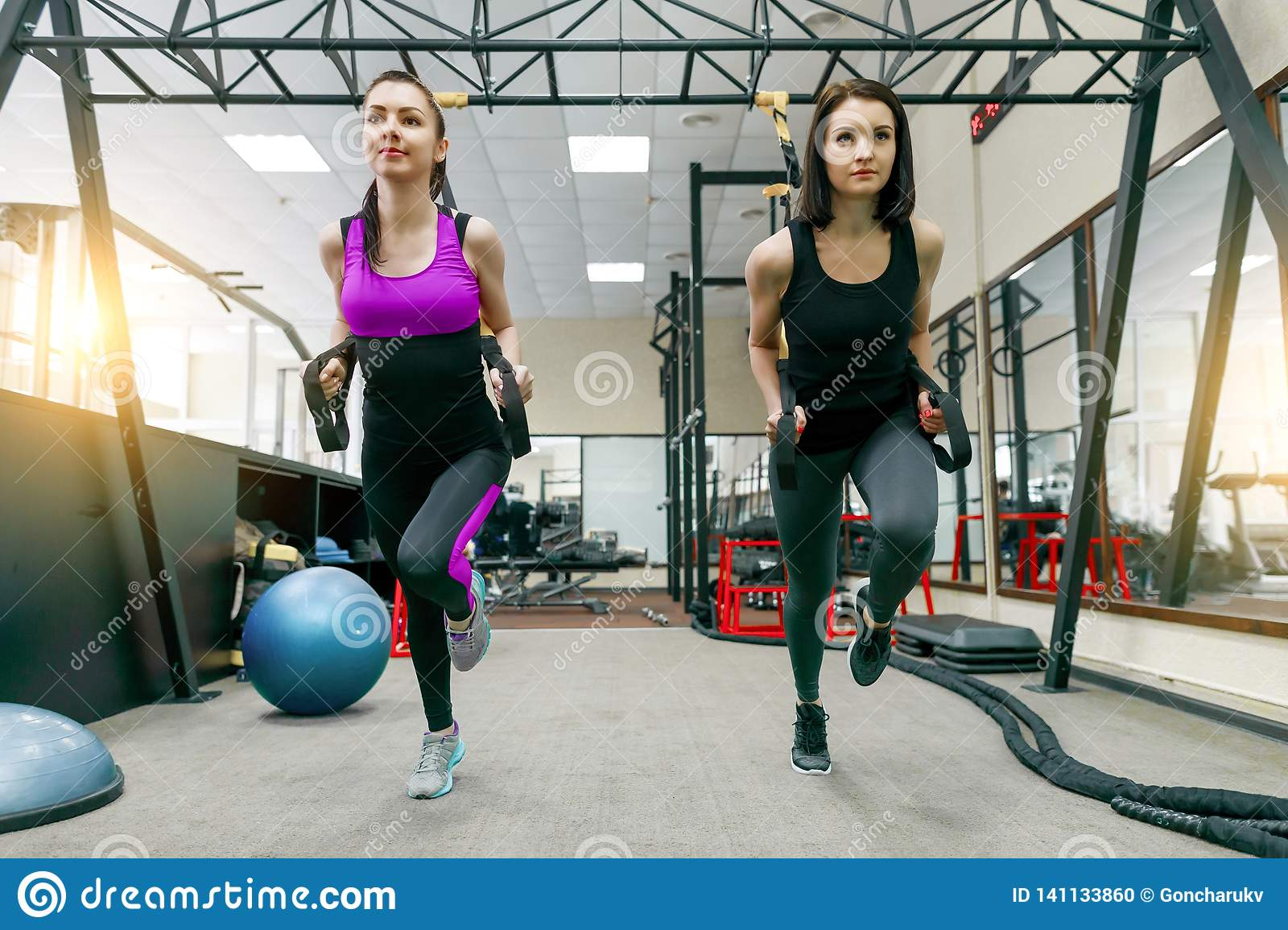 Group Training With Loops In Gym, Two Young Attractive Fitness Women Doing Cross  Fit With Straps System. Sport, Teamwork, Training Stock Photo - Image of  push, body: 141133860