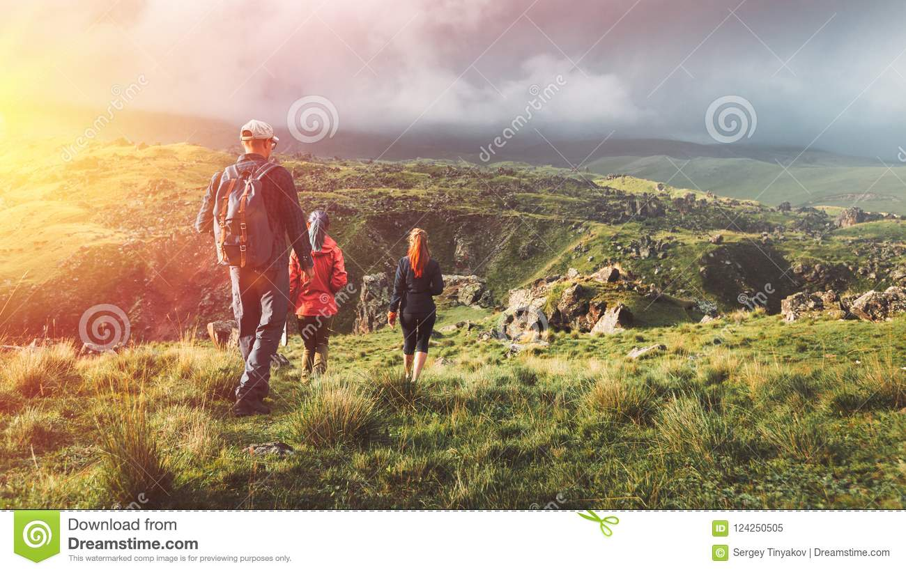 Group Of Hikers Walking Along The Green Hills, Rear View. Travel