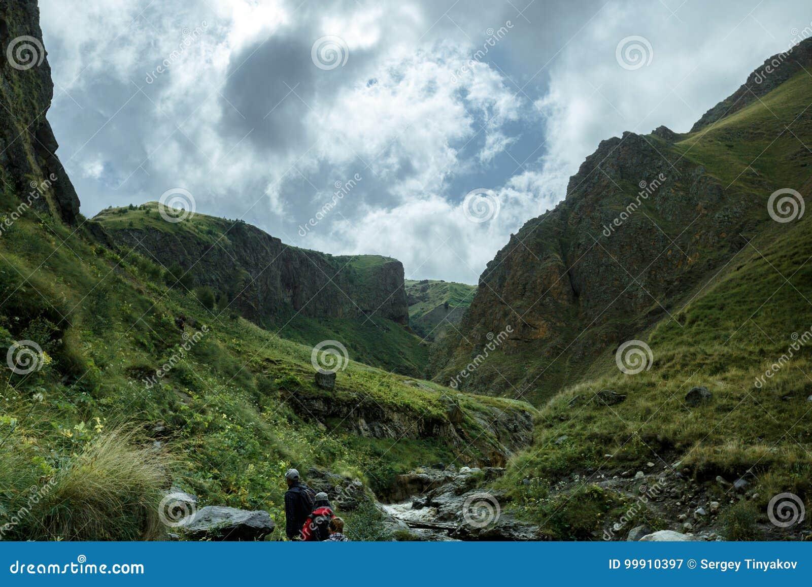 Group Of Travelers Walking Along In Summer Mountains, Journey Travel Trek Concept