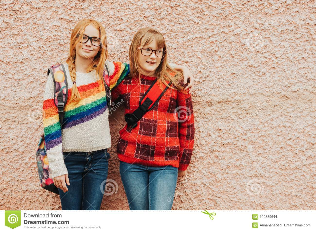 Group of two adorable kid girls with school backpacks wearing glasses