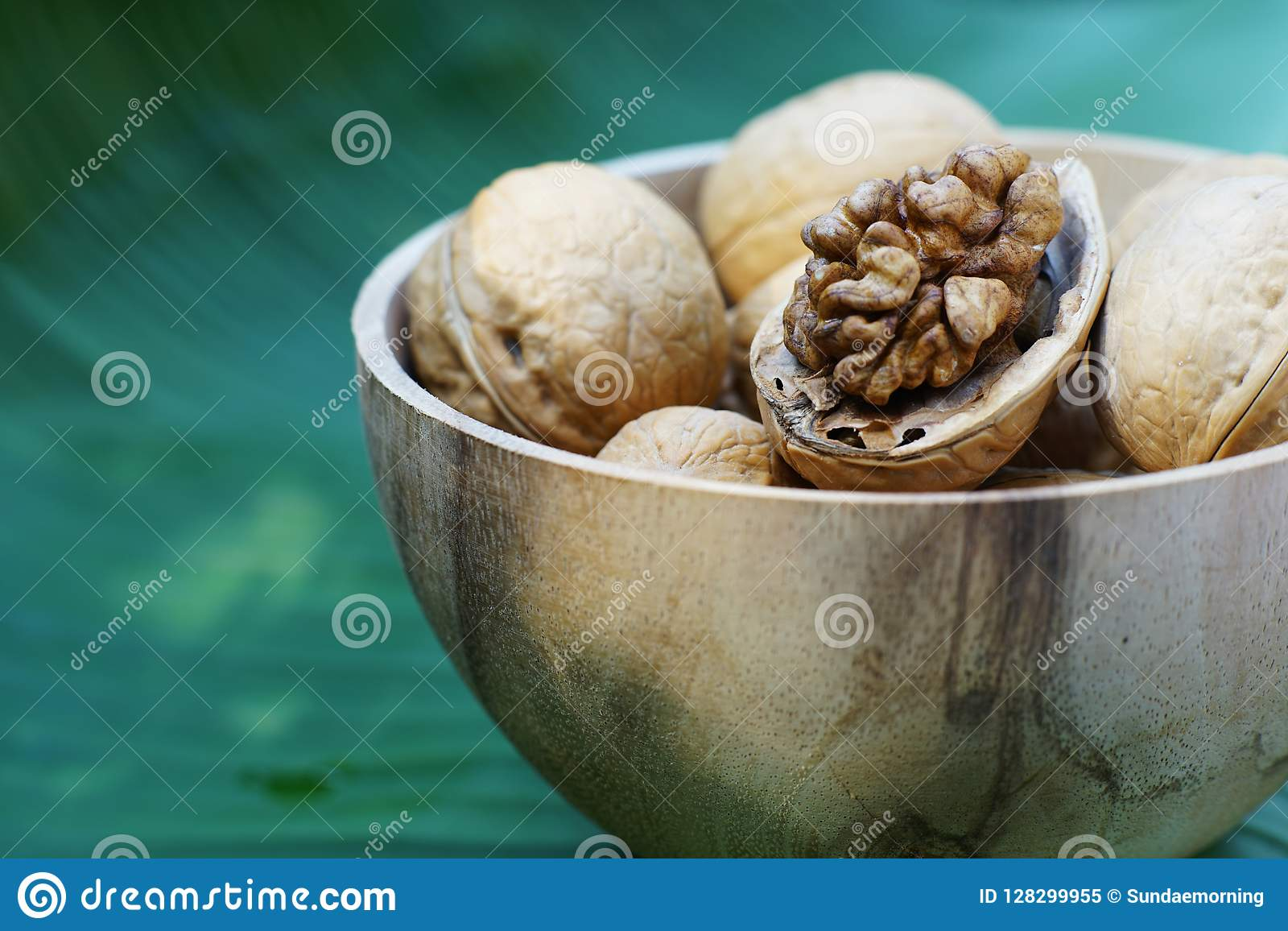 Group of walnut in wooden bowl on wood background, copy space, super food concept