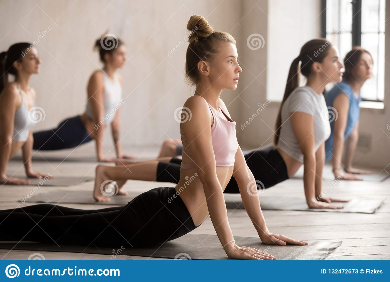 Group of women practicing yoga lesson, upward facing dog pose