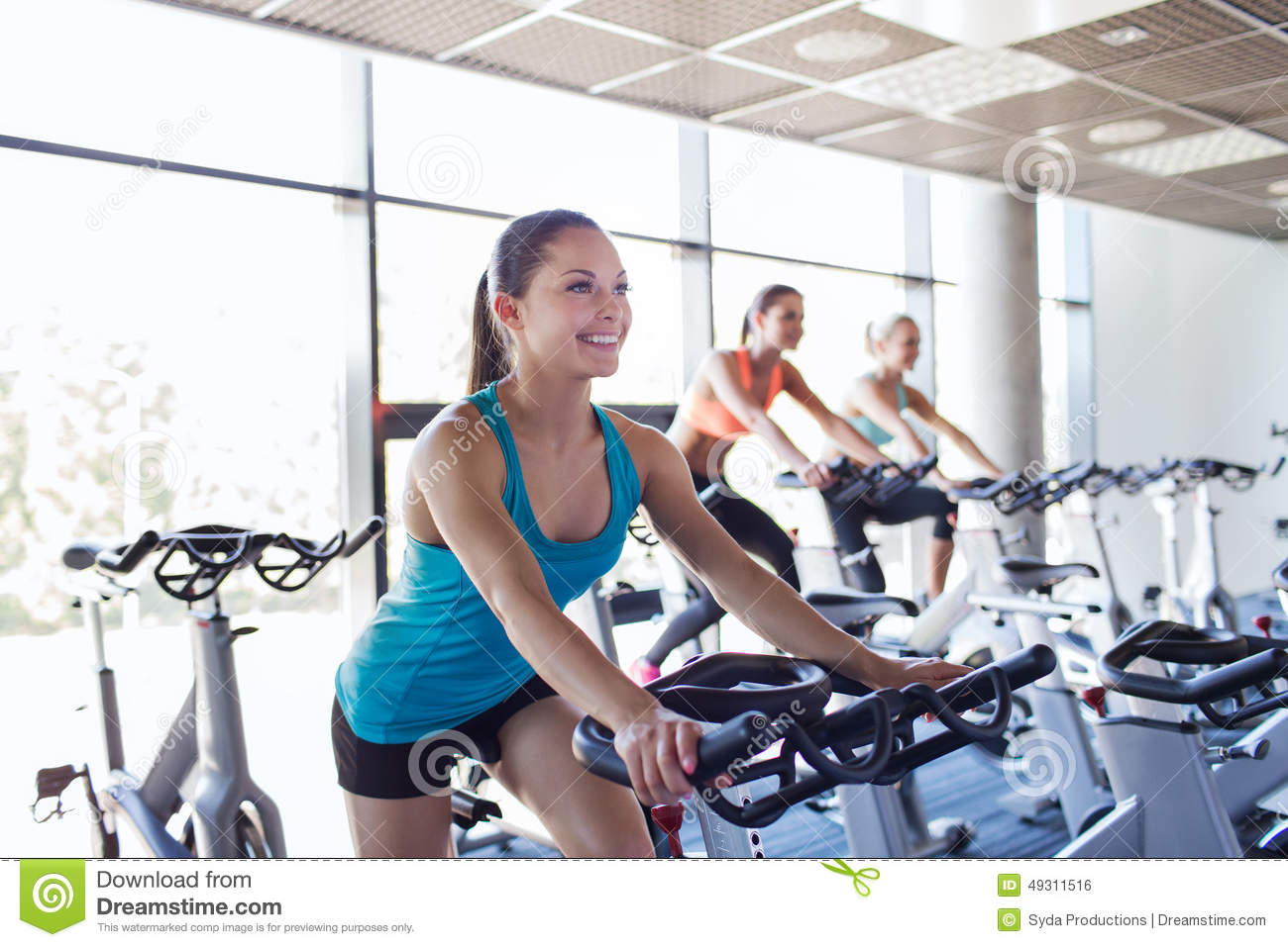 Group of women riding on exercise bike in gym stock photo for Fitness gym