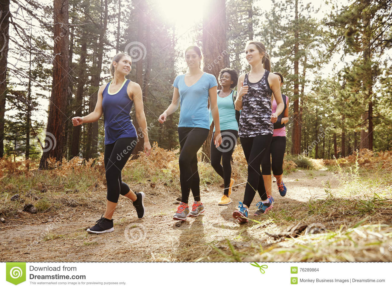Group of women runners walking in a forest talking, close up