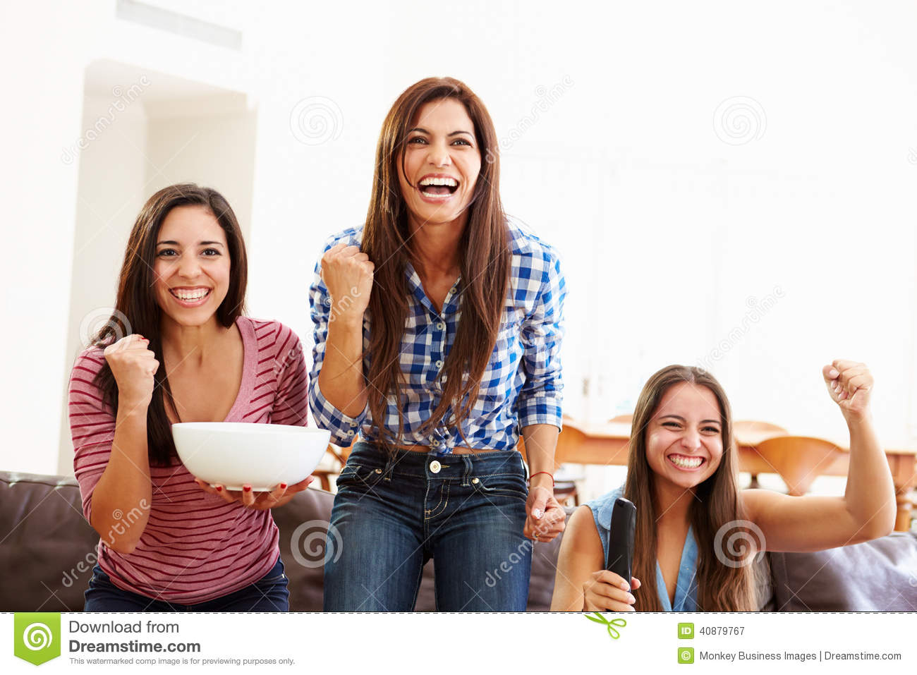 Group Of Women Sitting On Sofa Watching Sport Together ...