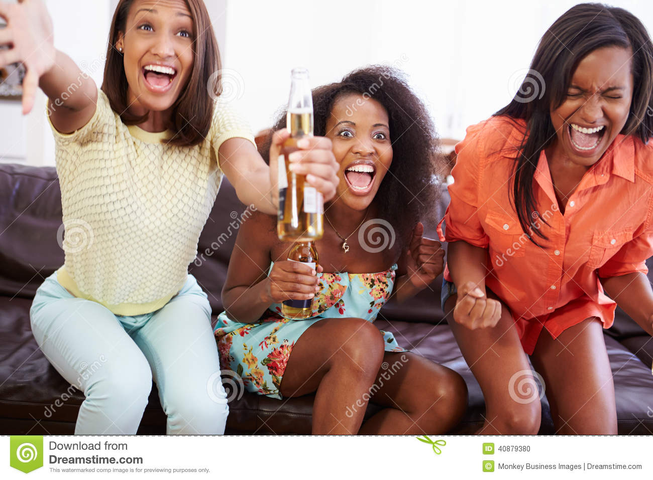 Group Of Women Sitting On Sofa Watching TV Together