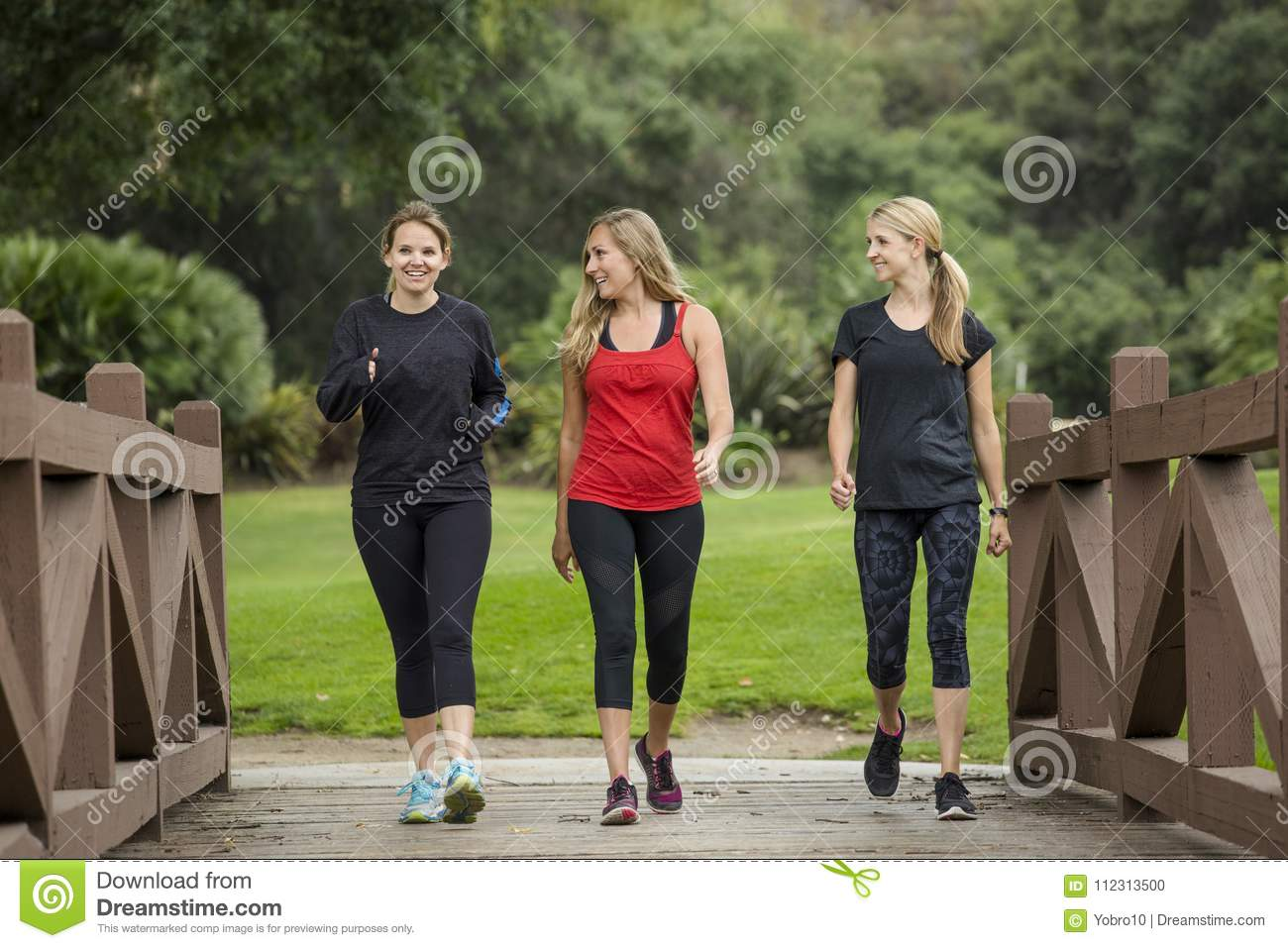 Group women in their 30s walking together in the outdoors.