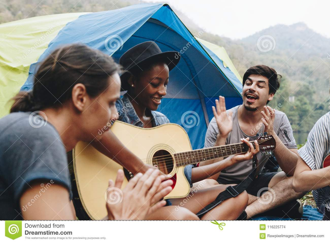 Group of young adult friends in camp site playing guitar