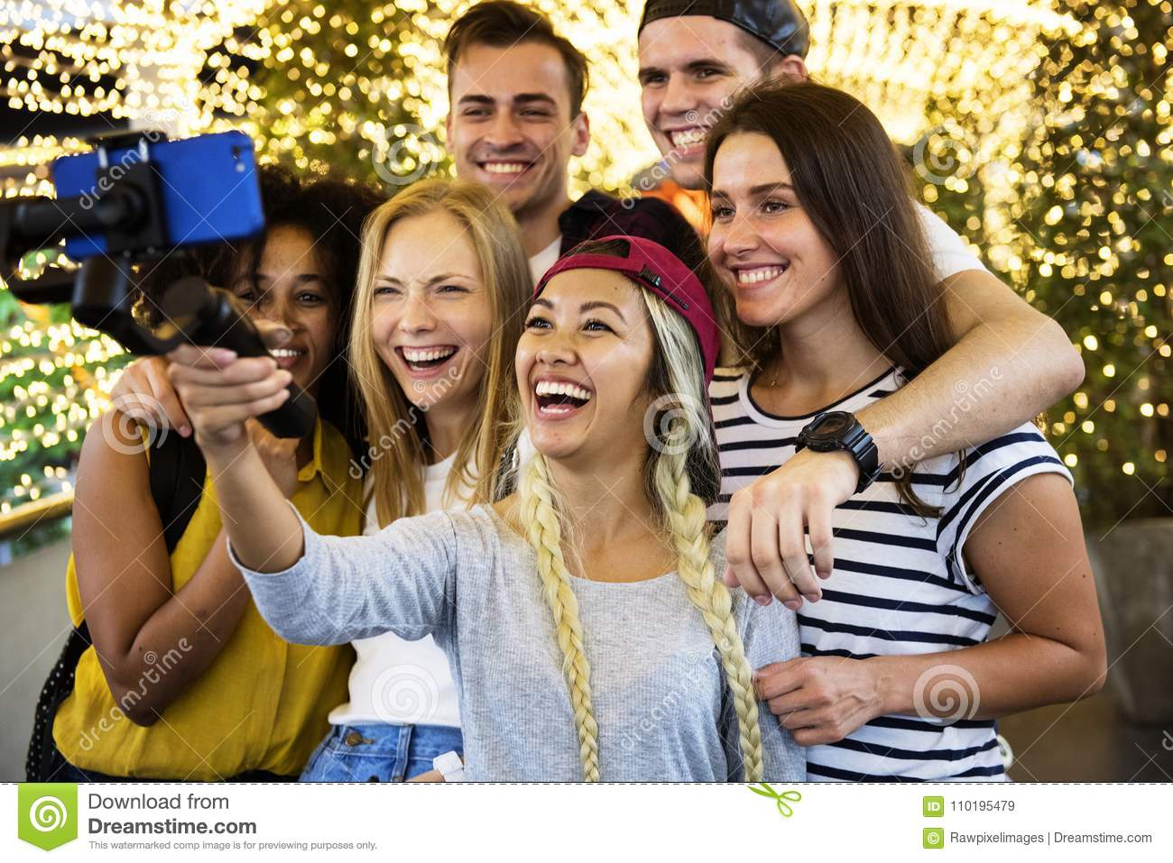 Group of young adult friends taking a group selfie with a selfie