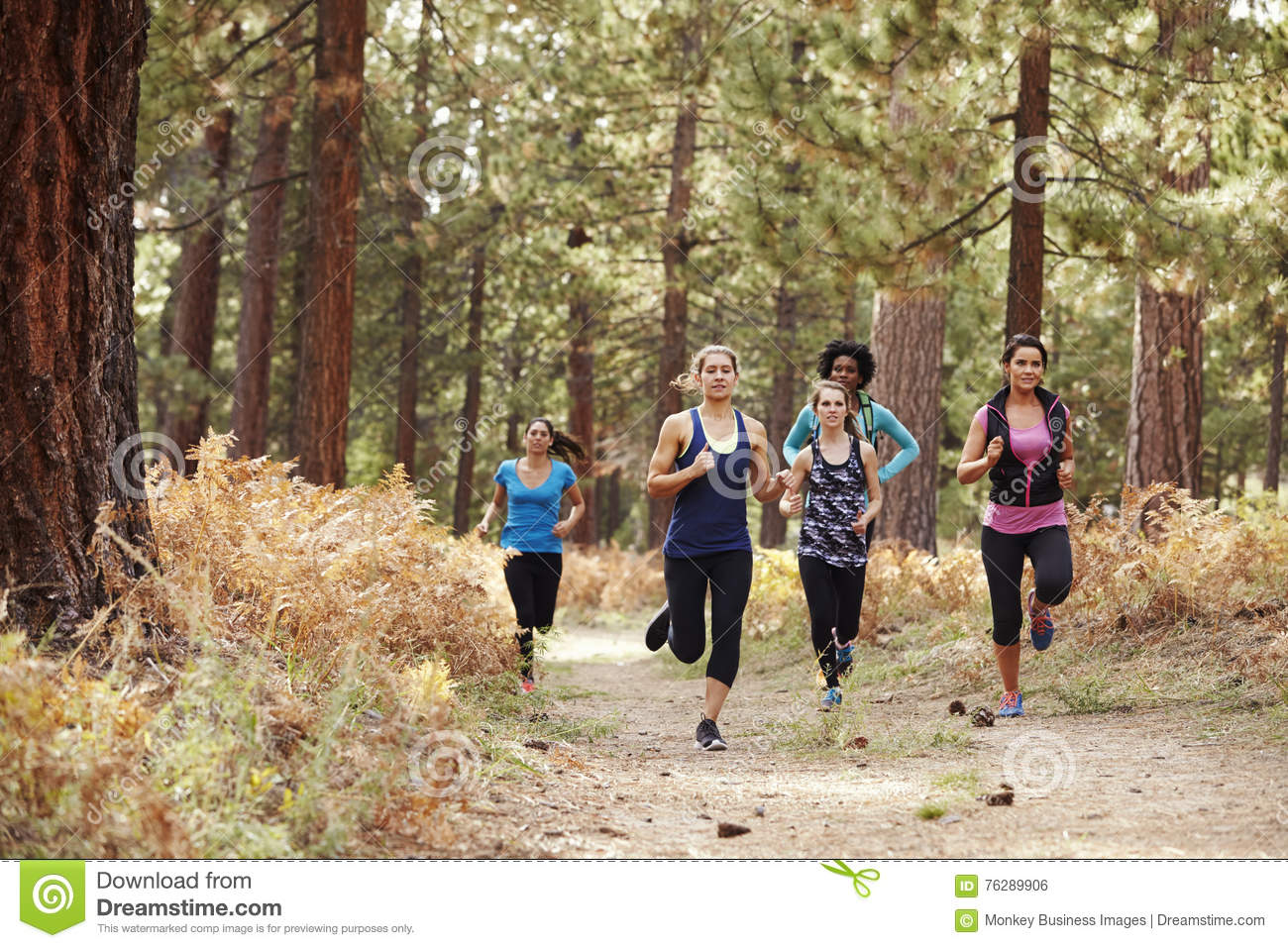 Group of young adult women running in a forest