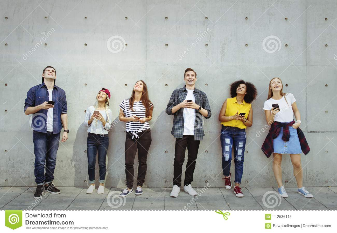 Group of young adults outdoors using smartphones looking up