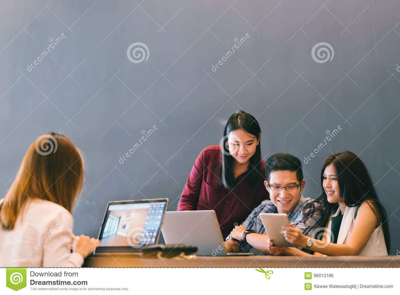 Group of young Asian business colleagues in team casual discussion, startup project business meeting or happy teamwork brainstorm
