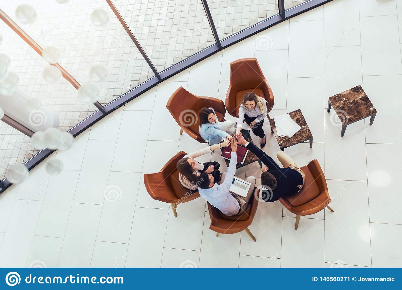 Group of young business professionals sitting together and having casual discussing in office hallway. Top view
