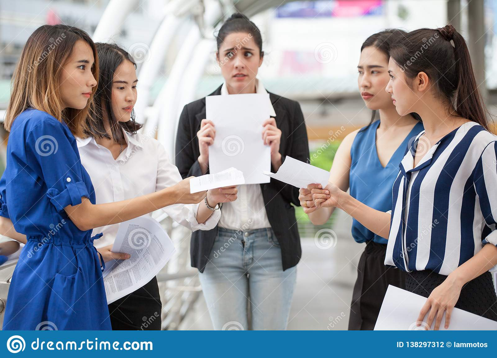happy young businesswoman is showing money and laptop with blank copy space screen and clipping path in urban city. girl holding
