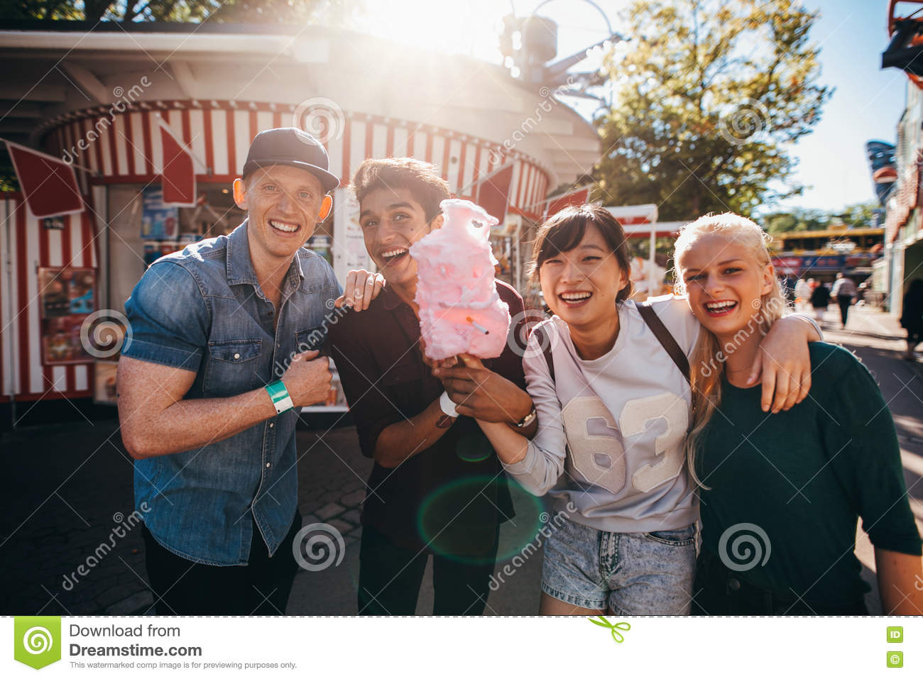 Group of young friends with cotton candy in amusement park